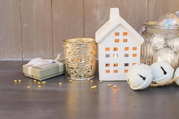 Decoraciones navideñas y casa de invierno blanca con luces brillantes y caja de regalo