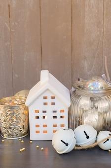 Decoraciones navideñas y casa de invierno blanca con luces brillantes, espacio de copia en tablones de madera gris