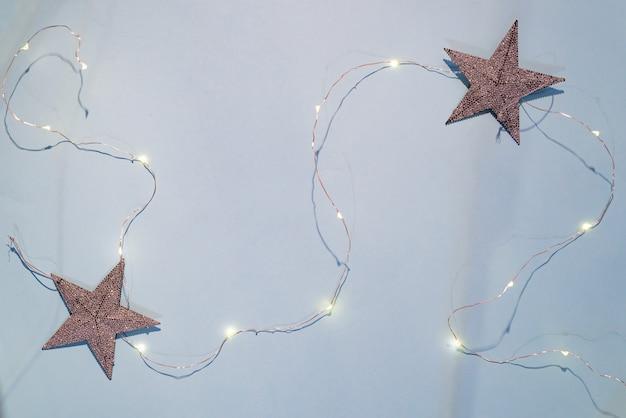 Decoraciones navideñas estrellas brillantes, guirnalda de navidad sobre un fondo azul