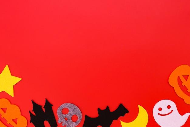 Decoraciones navideñas de halloween sobre fondo rojo, endecha plana de decoraciones de halloween en rojo, vista superior copia espacio, concepto de halloween.