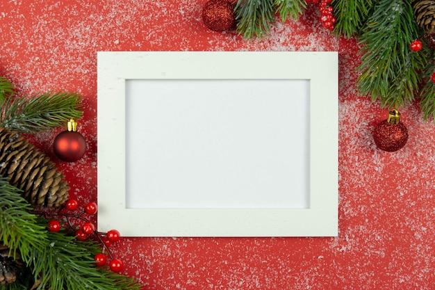 Decoraciones navideñas rojas y ramas de abeto con nieve y marco de fotos blanco sobre fondo rojo.
