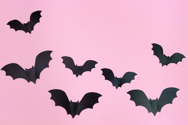 Decoraciones de papel de halloween murciélagos negros sobre fondo rosa pastel con espacio de copia. concepto de halloween.
