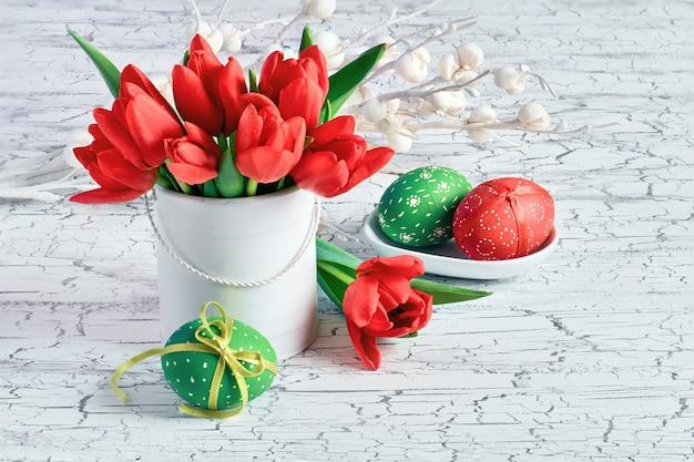 Decoraciones de pascua, tulipanes y huevos de colores, en colores rojo y verde.