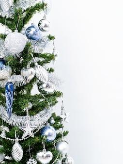 Decoraciones de plata de navidad en una rama de abeto sobre un blanco