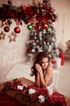 Decoraciones de vacaciones de invierno. colores cálidos. encantadora mujer morena vestida de beige