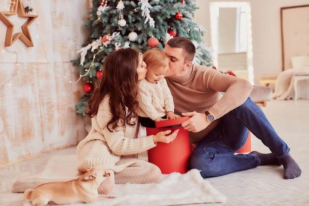 Decoraciones de vacaciones de invierno. colores cálidos. mamá, papá e hijita juegan con un perro.