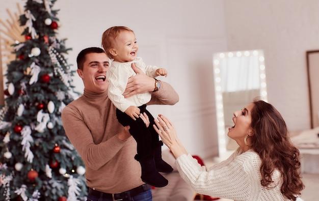 Decoraciones de vacaciones de invierno. colores cálidos. retrato familiar. mamá, papá y su pequeña hija.