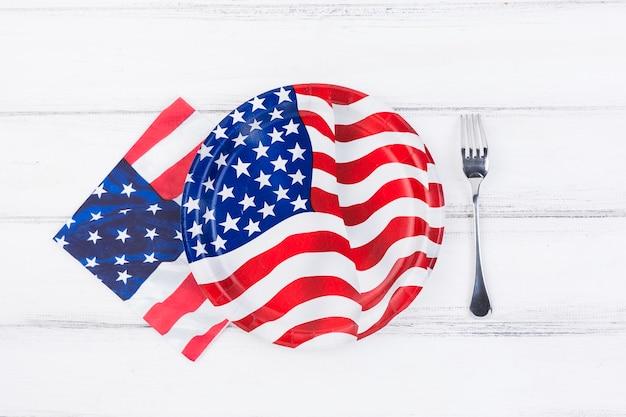 Decorado con placa de bandera de américa, servilleta y tenedor en mesa