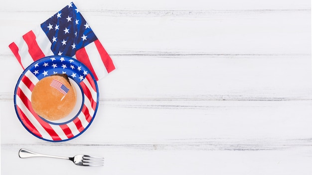 Decorado con placa de bandera de estados unidos, servilleta y tenedor en mesa