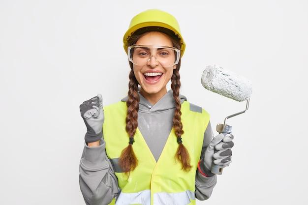Decorador femenino positivo aprieta el puño de alegría sostiene el rodillo de pintura listo para la renovación de la habitación