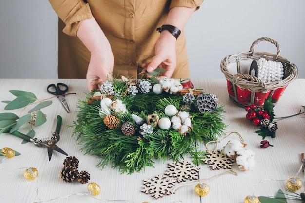 Decorador de floristería haciendo corona de navidad