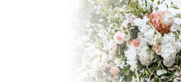 Decorar el arco con flores y telas para una ceremonia de boda en la naturaleza