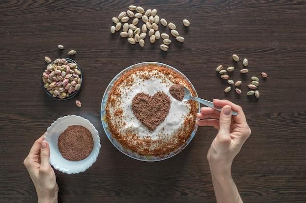 Decorar un pastel para el día de san valentín. tarta hecha a mano con glaseado de queso crema y un corazón de chocolate.