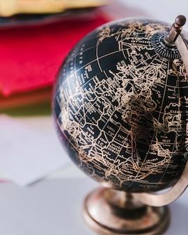 Decorativo globo negro y bronce sobre escritorio.