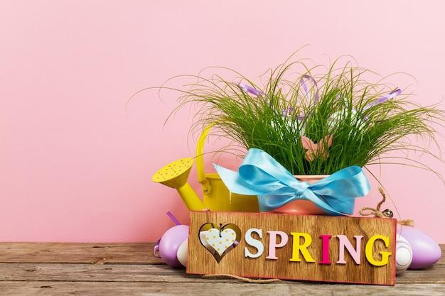 Decorativos huevos de colores en flor con hierba verde fresca en la mesa de madera sobre fondo de color rosa. horizontal con espacio de copia.