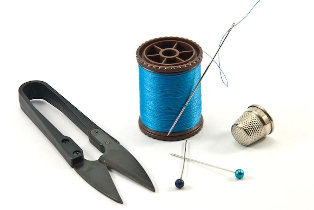 Dedal, agujas, carretes y tijeras para coser en un hilo de fondo