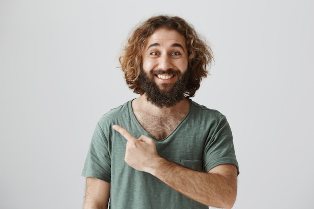 Dedo acusador alegre guapo del medio oriente en el anuncio