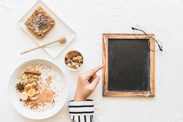 Dedo acusador femenino en la pequeña pizarra en blanco con desayuno saludable; panal y nueces