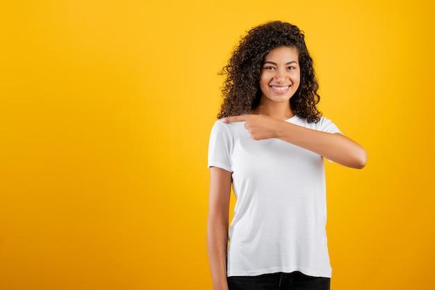 Dedo acusador sonriente de la muchacha negra en el copyspace aislado sobre amarillo