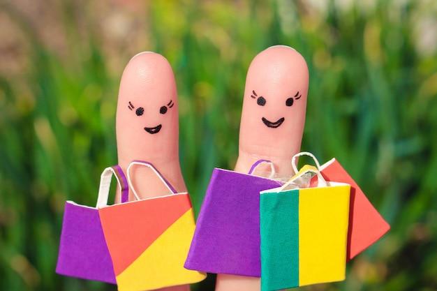 Dedo de arte de amigos felices con bolsas de la compra.