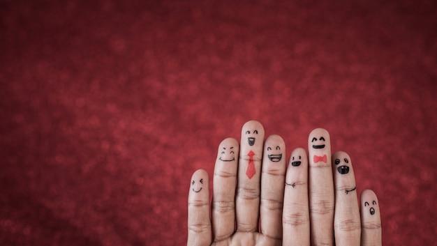 Dedo con emoción sobre fondo rojo