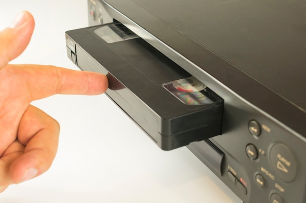 Dedo empujando un videocasete en el interior de una videograbadora para ver grabaciones