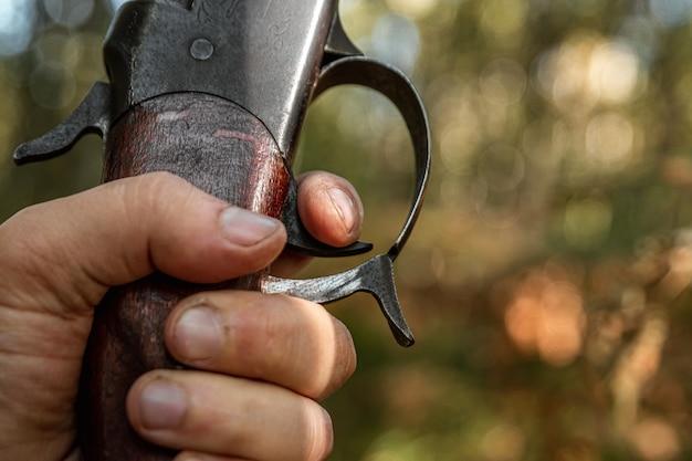 Dedo en el gatillo de un rifle de caza en el bosque de otoño