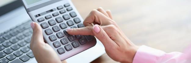 Dedo de la mujer presiona el botón en el primer plano de la calculadora