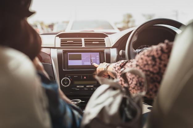 Dedo de mujer tocando una navegación de pantalla táctil en el salpicadero del coche