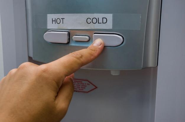Dedo presiona el botón de agua caliente de los refrigeradores primer plano