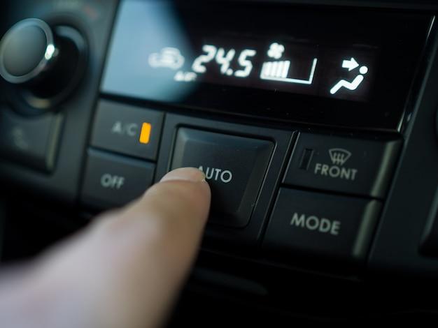 Dedo presiona el botón para encender el aire acondicionado en el coche