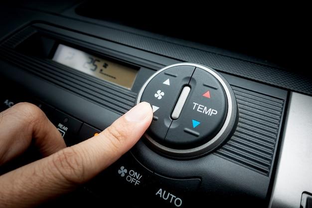 Dedo presionando en el interruptor del ventilador de un sistema de aire acondicionado del coche