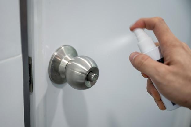 Dedo presionando spray de alcohol en el pomo de la puerta del inodoro. provenga la infección por coronavirus, desinfectantes covid-19