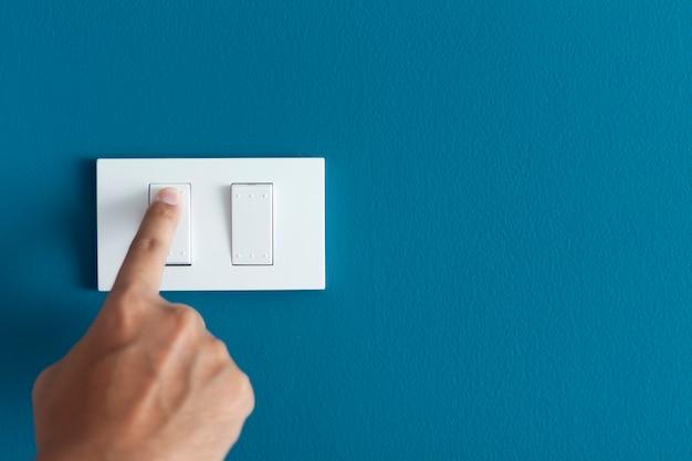 Un dedo que enciende el interruptor de encendido en bruto en la pared oscura azul.