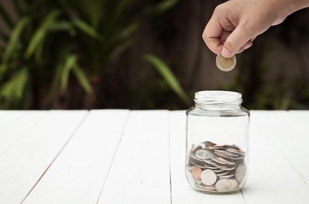 Dedo que sostiene el relleno de monedas en la botella de vidrio con monedas niveladas en la botella
