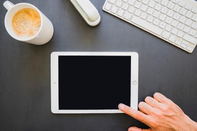 Dedo tocando la pantalla de la tablet en el trabajo