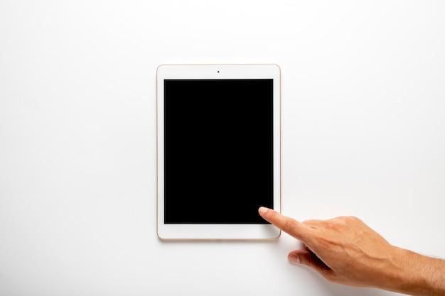 Dedo tocando la pantalla de la tableta plana