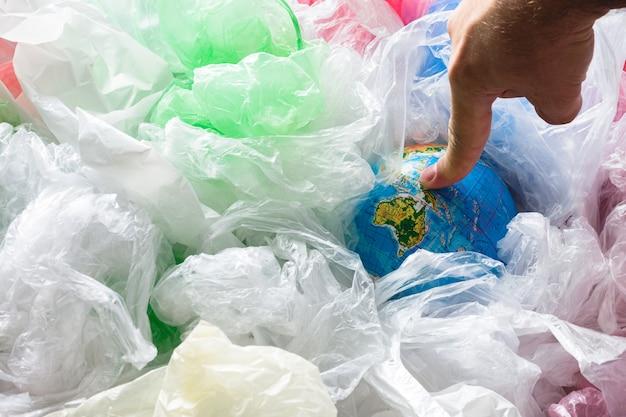 Dedo tocando la tierra rodeada de bolsas de plástico