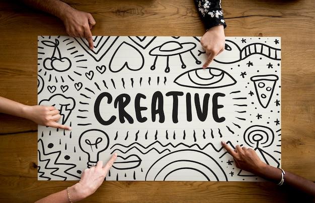 Dedos apuntando a una tipografía de idea creativa.