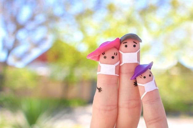 Dedos arte de familia con mascarilla en caminata.