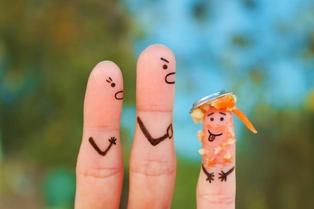 Dedos arte de la familia durante la pelea. el concepto de padres regaña al niño porque le puso un plato de comida en la cabeza.