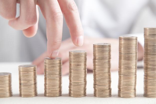 Dedos caminando sobre pilas de monedas. concepto de crecimiento