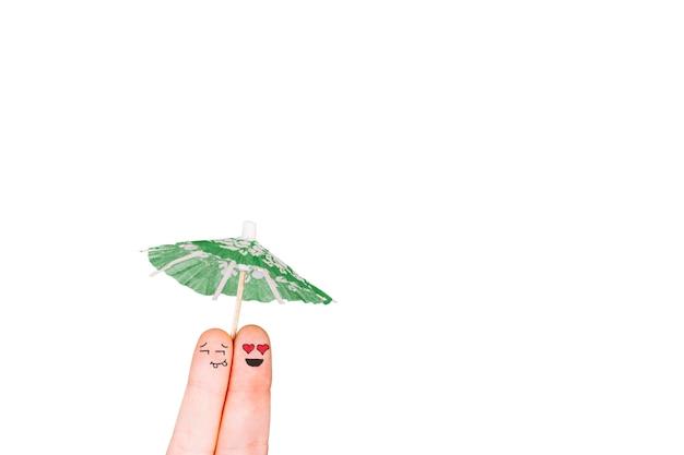 Dedos con caras sosteniendo paraguas