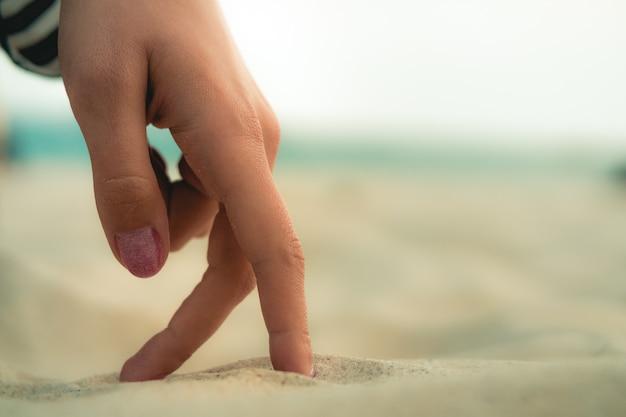 Dedos de las mujeres están caminando en la arena en la playa