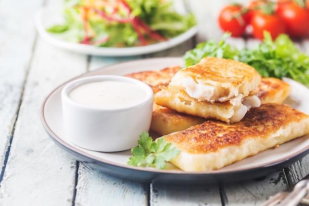 Dedos de pescado frito dorado desmenuzado servido con salsa tártara y ensalada en un blanco de madera rústica