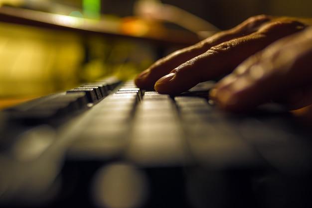 Dedos presionando en un teclado de computadora en la oscuridad.