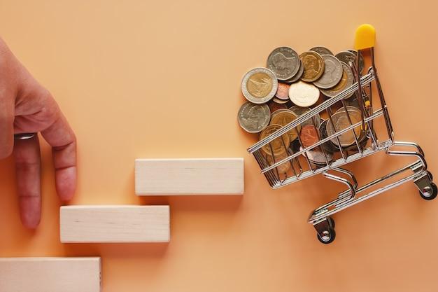 Los dedos que se mueven suben la escalera de juguete de madera al mini carrito de compras lleno de dinero