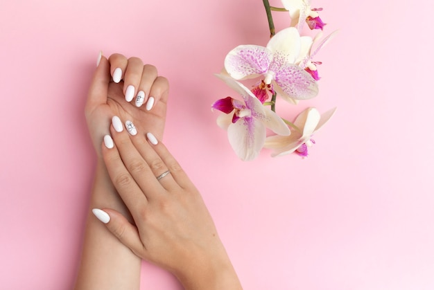 Dedos sutiles de las manos de una hermosa joven con uñas blancas sobre un fondo rosa con flores de orquídeas. spa, concepto de cuidado de las manos. banner con espacio de copia. manos femeninas con manicura y gel polaco