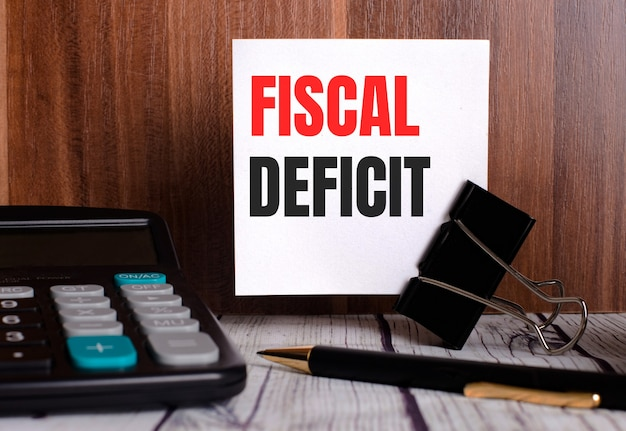 Déficit fiscal está escrito en una tarjeta blanca sobre un fondo de madera junto a una calculadora y un bolígrafo.