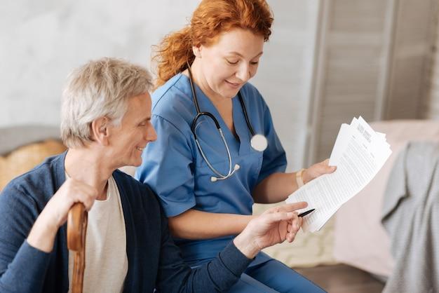 Definición de la causa de la enfermedad. increíble médico persistente positivo hablando con su paciente y explicándole algunos detalles de su tratamiento